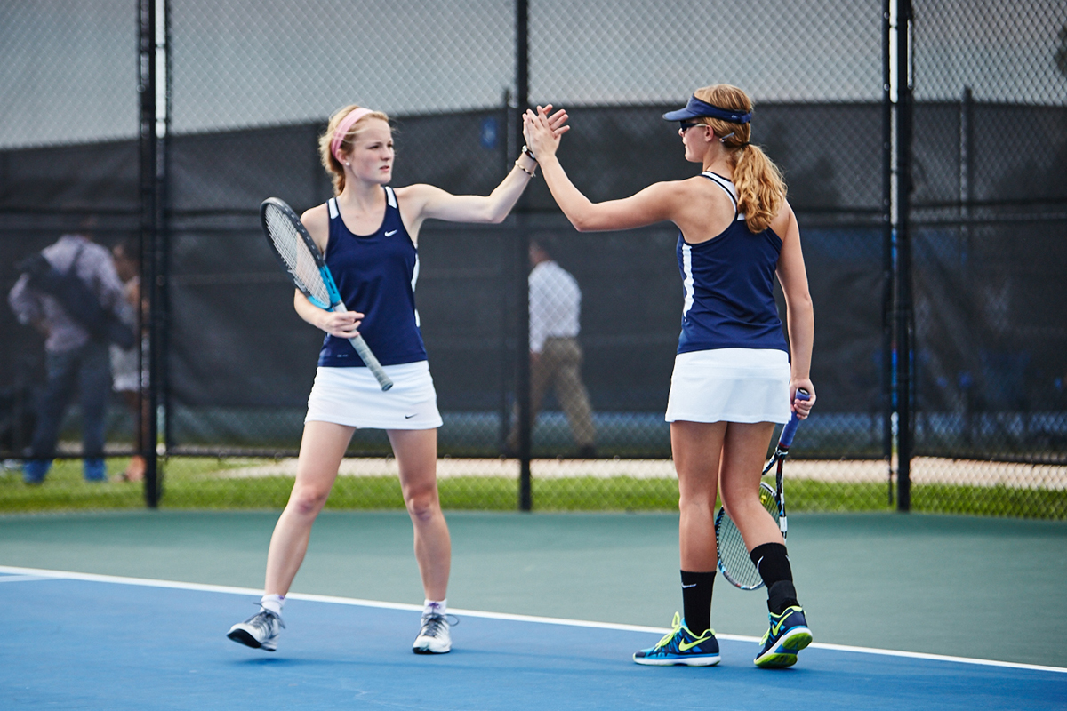 girls tennis players giving high five