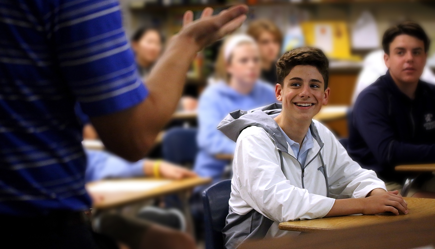 student smiling as teacher talks